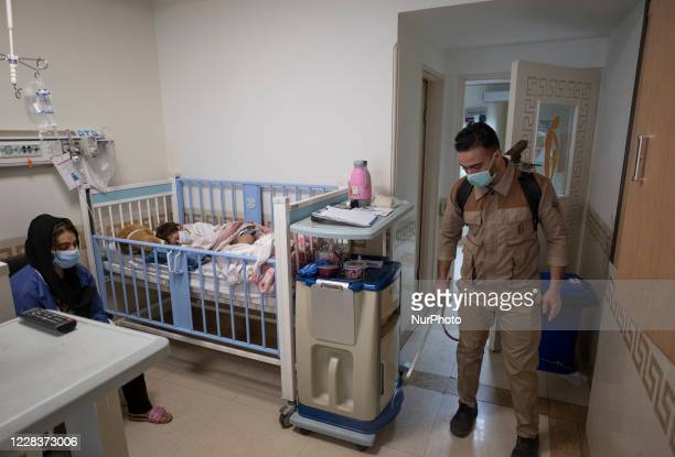 An Iranian hospital personnel sprays disinfectant to sanitize a room as 7yearold boy Mohammad Amin who is infected by the new coronavirus disease...