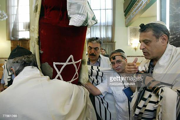 An Iranian Jew wearing a prayer shawl holds the Torah scrolls during the Morning Prayer ritual at a Tehran synagogue 06 July 2006 According to the...