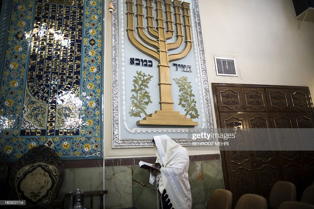An Iranian Jewish man wearing a Tallit, reads the Torah during morning prayer at Youssef Abad synagogue in Tehran on September 30, 2013. Present for more than 2,500 years in Persia, Iranian Jews have lost more than 70 percent of their 80,000 to 100,00 population who lived in Iran prior to the 1979 Islamic revolution, today Iran is home to some 8,750 Jews, according to a 2011 census. They are scattered across the country, but are mostly in the capital Tehran, Isfahan in the center, and Shiraz in the south.