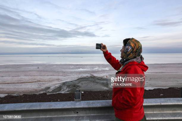 An Iranian journalist uses her phone to take a picture of the salt lake of Urmia in the country's northwest which had been shrinking in one of the...