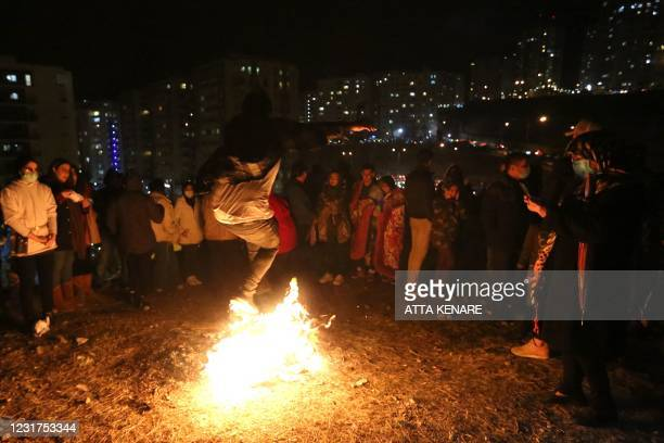 An Iranian jumps over the bonfire in Tehran on March 16, 2021 during the Wednesday Fire feast, or Chaharshanbeh Soori, held annually on the last...