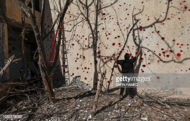 An Iranian Kurdish Peshmerga member of the Kurdistan Democratic Party of Iran I sprays red paint at holes in a wall made by shrapnel from a rocket...