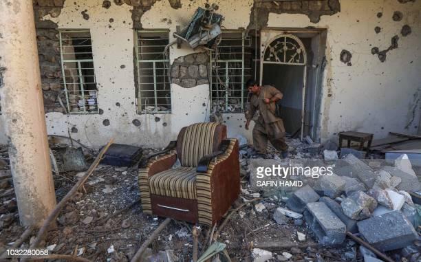 TOPSHOT An Iranian Kurdish Peshmerga member of the Kurdistan Democratic Party of Iran inspects damage at the party headquarters in Koysinjaq 100...