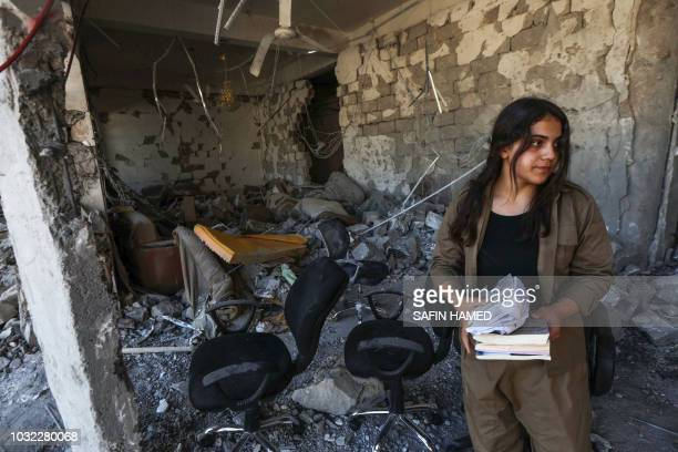 An Iranian Kurdish Peshmerga member of the Kurdistan Democratic Party of Iran collects books while inspecting damage at the party headquarters in...