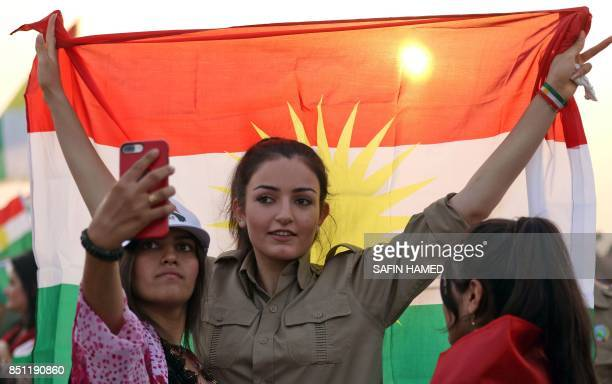 An Iranian Kurdish woman holds a Kurdish flag as she takes part in a gathering to urge people to vote in the upcoming independence referendum in the...