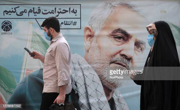 An Iranian man and a veiled woman wearing protective face masks walk past a portrait of the former commander of Irans Islamic Revolutionary Guards...