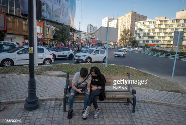 An Iranian man and a woman use a smartphone while sitting on a street-side in downtown Tehran on May 28, 2021. Iranians will vote to elect the new...
