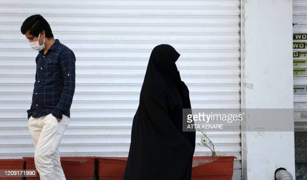 An Iranian man and a woman wearing a protective face masks against the novel coronavirus walk past a closed shop in the capital Tehran on April 5...