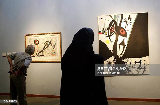 An Iranian man and woman observe Spanish painter Joan Miro's paintings Le Matador and Oiseaux Des Grottes displayed at the Modern Art Movement...