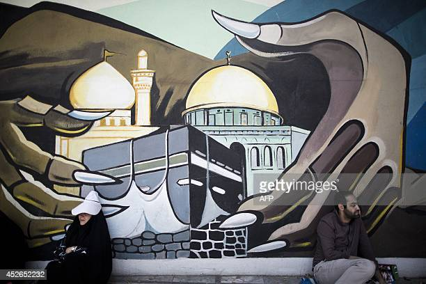 An Iranian man and woman sit under a mural bearing the holy Kaaba of Mecca and Dome of the Rock of Jerusalem at Palestine square as they wait for the...