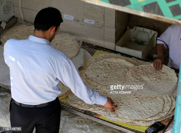 An Iranian man buys loafs of bread at a bakery in the Iranian capital Tehran on June 15 2019 US President Donald Trump last year withdrew from the...