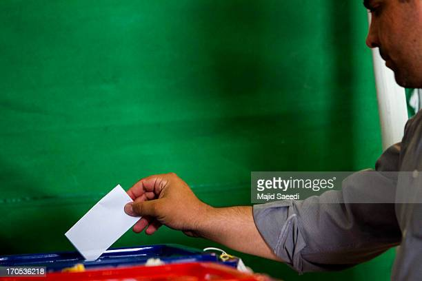An Iranian man casts his vote in a ballot box at a polling station during the first round of the presidential election on June 14 2013 in Tehran Iran...
