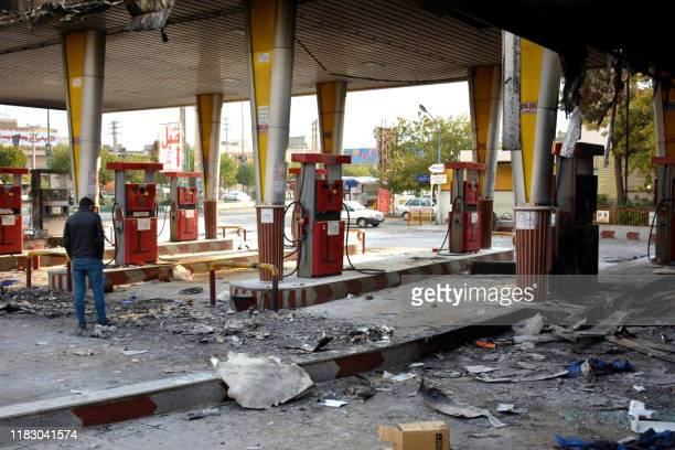An Iranian man checks a scorched gas station that was set ablaze by protesters during a demonstration against a rise in gasoline prices in...