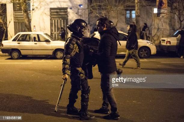 An Iranian man confronts a policeman during a demonstration outside Tehran's Amir Kabir University on January 11, 2020. - Demonstrations broke out...