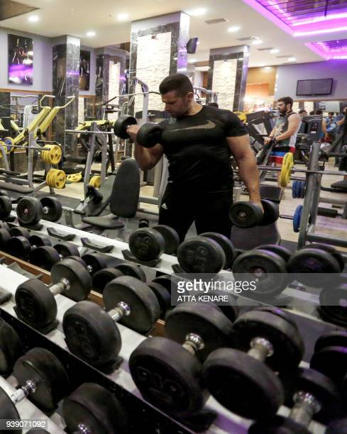 An Iranian man exercises with dumbbells in a modern gym in the capital Tehran on February 27 2018 A few streets and several centuries apart Iran's...