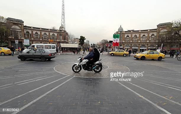 An Iranian man gives a ride to a woman in the back on a motorcycle at Hafez square in central in Tehran on February 29 2016 / AFP / ATTA KENARE