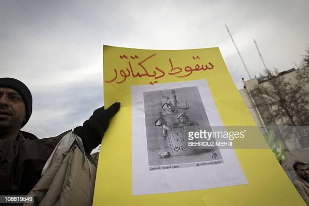 An Iranian man holds a cartoon depicting Egyptian President Hosni Mubarak joining Iran's late shah Mohammad Reza Pahlav and executed Iraqi dictator...
