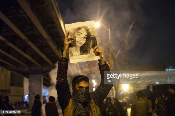 An Iranian man holds a picture of a victim of the Ukrainian Boeing 737800 plane crash during a demonstration in front of Tehran's Amir Kabir...