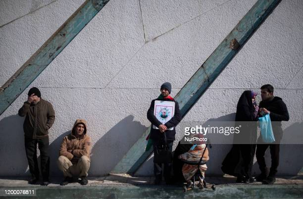 An Iranian man holds a portrait of the Former Islamic Revolutionary Guards Corps Qods Force Qasem Soleimani during a rally to mark the Islamic...