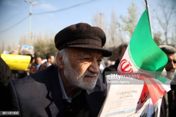An Iranian man holds an Iranian flag during a protest after performing the Friday Prayer at Imam Khomeini Mosque following US' statement about...