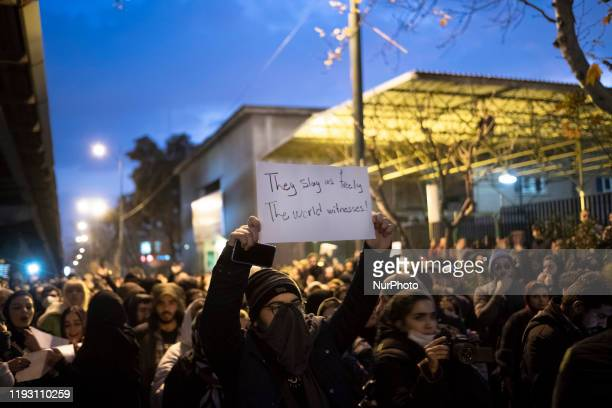An Iranian man holdsup a placard as he attends in front of a University to mark the memory of the victims of the Ukraine Boeing 737 passenger plane...