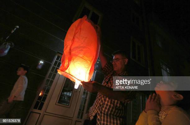 An Iranian man lights a lantern outside their houses in Tehran on March 13 2018 during the Wednesday Fire feast or Chaharshanbeh Soori held annually...