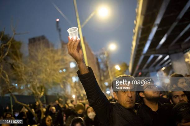 An Iranian man lights candle in memory of the victims of the Ukraine Boeing 737 passenger plane, in front of a University in Tehrans business...