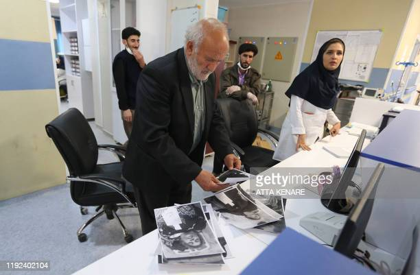 An Iranian man looks at pictures of victims at an information office of a hostpial in the southeastern Iranian city of Kerman as part of an...