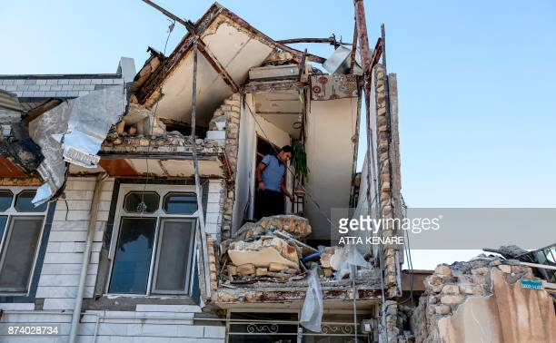 TOPSHOT An Iranian man looks through the damaged stairwell of a building in the town of Sarpole Zahab in the western Kermanshah province near the...