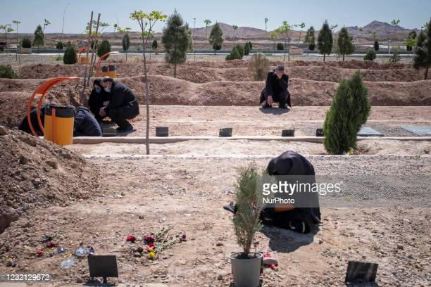 An Iranian man mourns while sitting near the grave of his father who has died from coronavirus disease, in the Benhesht-e-Masoumeh cemetery in the...