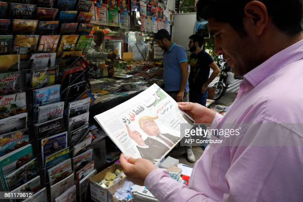 An Iranian man reads a copy of the daily newspaper 'Aftab' bearing a caricature of US President Donald Trump with a headline that reads in Persian...
