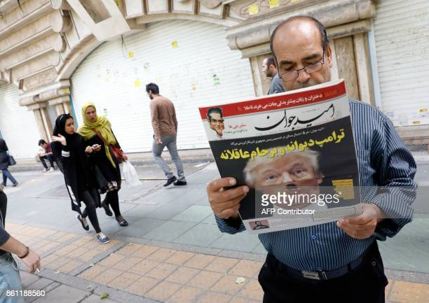 An Iranian man reads a copy of the daily newspaper 'Omid Javan' bearing a picture of US President Donald Trump with a headline that reads in Persian...