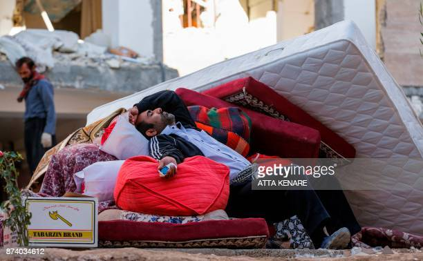 An Iranian man rests as he lies atop salvaged mattresses and items outside damaged buildings in the town of Sarpole Zahab in the western Kermanshah...