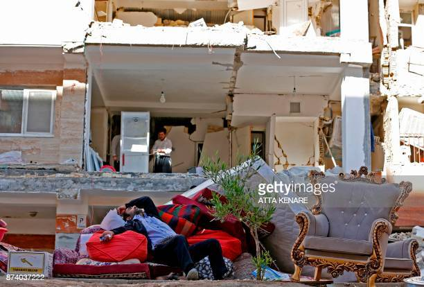 TOPSHOT An Iranian man rests as he lies atop salvaged mattresses and items outside damaged buildings in the town of Sarpole Zahab in the western...