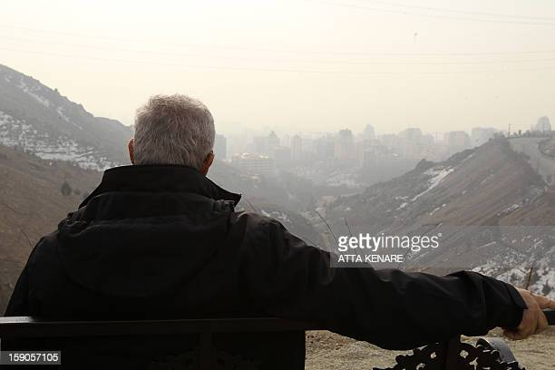 An Iranian man sits on a bench in the Tochal mountainous area overlooking the polluted skyline of the capital Tehran on January 72013 Air pollution...