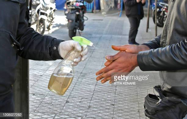 An Iranian man sprays alcohol on the hands of people outside an office building in Tehran on March 4 2020 Iran has scrambled to halt the rapid spread...
