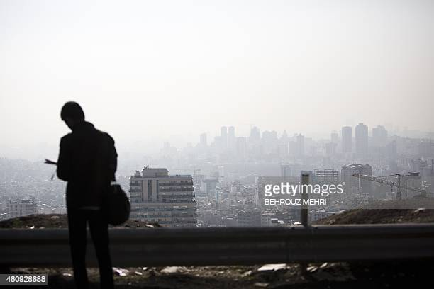 An Iranian man stands in front of a general view of the north of Tehran engulfed in a cloud of smog caused by pollution on December 31 2014 Almost...