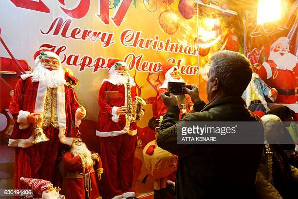An Iranian man takes a picture of Christmas decorations outside a shop in the capital Tehran on December 24 on Christmas eve / AFP / ATTA KENARE
