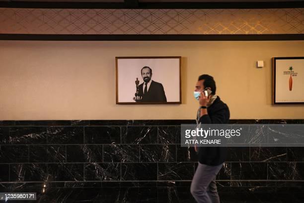 An Iranian man talks on his phone as he walks past a poster of Oscar-winning Iranian director Asghar Farhadi on the opening day of the 38th Tehran...