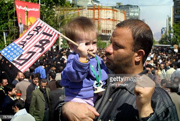 An Iranian man teaches his son the 'death to America' chant during a demonstration after Friday prayers April 5 2002 in Tehran The protesters opposed...