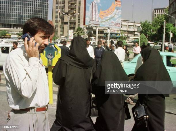 An Iranian man uses his mobile phone in downtown Tehran 18 May 2000 as women covered in line with the strict Islamic dress code imposed since the...