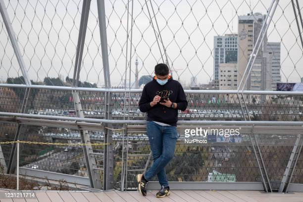 An Iranian man uses his smartphone while standing on a bridge that is equipped with a Huawei 5G modem in the Water and Fire park in northern Tehran...