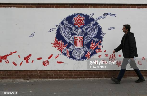 An Iranian man walk past a mural painted on the walls of the former US embassy in the capital Tehran on January 4 one day after Soleimani and other...