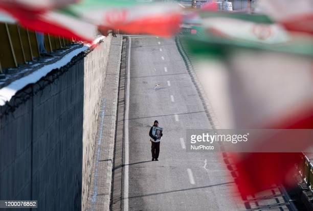 An Iranian man walks along the Azadi avenue as he carries a portrait of the Former Islamic Revolutionary Guards Corps Qods Force Qasem Soleimani...