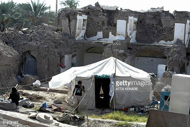 An Iranian man walks out of his tent erected in front of destroyed buildings 05 November 2004 in the southeastern devastated city of Bam where a...
