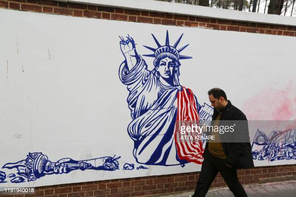 An Iranian man walks past a mural painted on the walls of the former US embassy in the capital Tehran on January 4 one day after Soleimani and other...