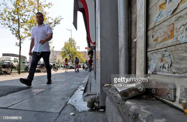 An Iranian man walks past a shuttered store in the capital Tehran, on July 20 as authorities tighten restrictions amid the COVID-19 pandemic. - Iran...