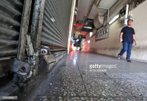 An Iranian man walks past shuttered stores at a commercial centre in downtown Tehran on July 20, 2021. - Iran a day earlier announced strict curbs in...