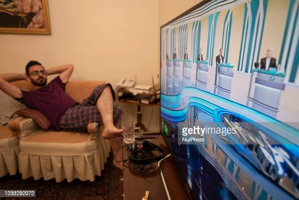 An Iranian man watches the first live televised debate between Irans June 18 presidential election candidates, at an apartment in downtown Tehran on...