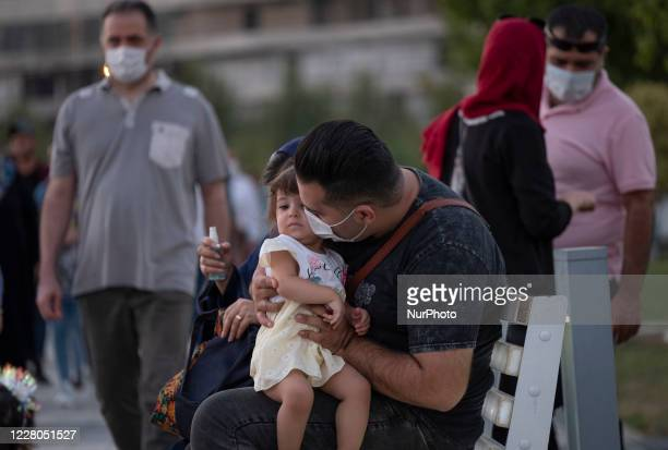 An Iranian man wearing a protective face mask kisses his kid as he sits on a bench in the recreational Chitgar artificial lake complex in...